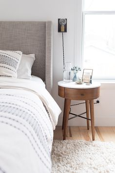 Clean and bright bedroom with marble topped bedside table in Washington DC