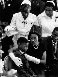 Widow of slain Civil Rights activist Medgar Evers comforts her grieving son Darrell during the funeral. Photo by John Loengard.