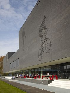 A sports college in Eindhoven featuring a black brick exterior with perforations in the shape of athletes.