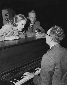 Medium BTS shot of Grace Kelly who plays Tracy Samantha Lord, Bing Crosby who plays C.K. Dexter-Haven and composer Saul Chaplin playing piano.