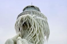 photos by thomas zakowski at the st. joseph north pier on the coast of lake michigan, where crashing winter waves have covered two lighthouses and the connecting bridge in ice.