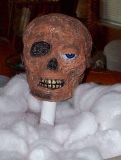Zombie head - Dollar Store flocked skull, Elmer's Glue, toilet paper (or Kleenex), Dollar Store eyeball, and craft paint.