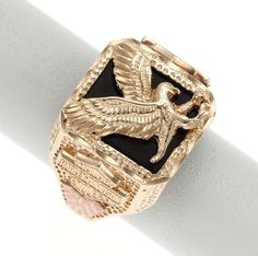 A gold ring set with black onyx, emblazoned with a gold eagle on the face. Ring sides are enhanced with rose gold and Harley-Davidson crests and emblems.