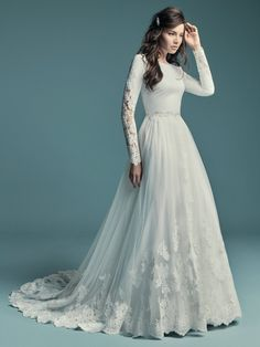 Maggie Sottero - OLYSSIA, This elegant sleeved wedding dress is comprised of Talin Stretch Crepe. Featuring a bateau neckline, scoop back, and lace illusion along the long sleeves. Finished with covered and crystal buttons over zipper closure. Detachable overskirt accented in lace sold separately.