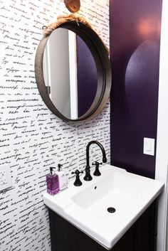 Round mirror reflects eggplant wall color against handwriting wallpaper above black and white vanity. (purple bathroom)
