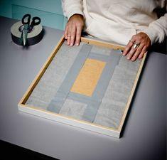 Étape 4 de la réalisation d'un mur insonorisé : placer le dos du cadre tendu de tissu dans le cadre et replier les clips pour le maintenir en place.