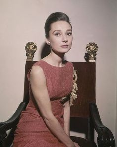 """The actress Audrey Hepburn photographed by Jim Pringle at the Hotel Hassler, at Piazza Trinità dei Monti, in Rome (Italy), on January 08, 1960.  Audrey was wearing:Cocktail dress: Givenchy (adorned in the front by a brooch, a sleeveless dress of voided velvet in a shade of red, detail of the neckline in back in a deep """"V"""", liner of silk in the same shade, of his haute couture collection for the Autumn/Winter 1959/60)."""