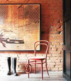 exposed brick wall, awesome print, and not to mention one of the coolest chairs.