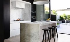 modern contemporary kitchen with Calcutta marble island bar bench top, marble range hood, stools, white pedant light, black and white cupboards cabinets