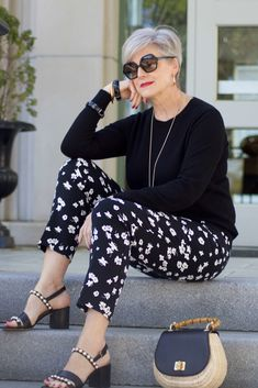 beth from Style at a Certain Age wears black and white floral ankle pants, black crewneck sweater, black pearl embellished sandals, and straw handbag