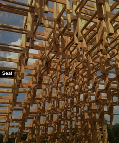 SEAT is composed of approximately 400 simple wooden chairs arrayed and stacked in a sine wave surface drawn into an agitated vortex rising from the ground.