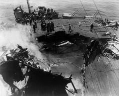 11th May 1945: Overhead view of the gaping hole in the deck of the USS 'Bunker Hill' after it was dive-bombed by two Japanese Kamikaze planes off the shores of Okinawa, Japan, during World War II. US soldiers stand near the smoking wreckage; 392 men were killed or remained missing, and 264 were wounded from the attack. The ship was sailing from Kyushu to aid in the US invasion of Okinawa. (Photo by US Navy/Getty Images)