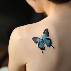 Small blue butterfly tattoo on the left shoulder blade. Tattoo...
