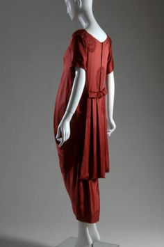 1917.Dress of red silk brocade. Scooped neck; short sleeves; draped and pleated panel extending from back of waist. Falls just below the knee.