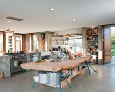 A massive slab of cypress perched atop sawhorses provides storage for pots and utensils. Tagged: Kitchen, Wood Counter, and Concrete Floor. Photo 3 of 23 in Fertile Grounds