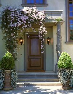 It is amazing how trailing flowers can add a sense of romance to any spot. Here, the simple and symmetrical entrance of this Mediterranean home is softened by the Clematis, cascading from the front porch in pink swathes delicately swaying in the summer br
