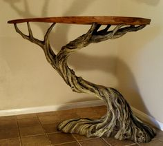 The Deadwood Table    A raw slab of oak sits atop a twisted old tree in this striking combination of natural and faux wood. The Deadwood Table is a one of a kind functional sculpture that will make a great accent table in any room.