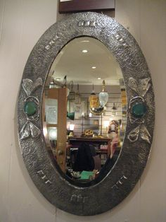 Glasgow style beaten pewter oval mirror with twin butterflies and Ruskin roundels