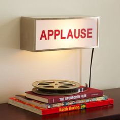 Applause Light Box, no longer available through PB Teen but could easily be made with a light box hung and vinyl lettering added. Wooden box with frosted plastic cover with a light kit inside would work as well. Fun for a media room or den.