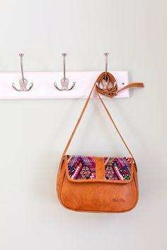 "•100% genuine leather •One zip pocket •Adjustable strap •Fabric liner •Hand embroidered huipil textile made from natural dyes •Handcrafted in Guatemala   9"" x 6.3"""