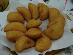 Do avental ao salto alto: Rissoles de queijo - 5 = xícaras de (chá) de água 1 = colher de (sopa) de margarina 2 =dentes de alho amassado 1/2 = cebola ralada 2 = cubos de caldo de galinha 1 = batata grande ou duas pequenas cozida e amassada 4 = xícaras de (chá) de farinha de trigo (talvez necessite de mais um pouquinho) 1 = ovo batido Farinha de rosca para empanar