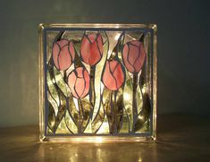 A brilliant stained glass light to enjoy in two different patterns. Done on both sides of a glass block in shades of greens, grays, pink and clear textured glass. One side a tulip bouquet and the other an abstract in the same colors. Photos were taken outdoors and indoors with the