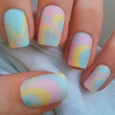 Water marble nail art design in baby pink, yellow and blue colors.