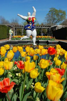 'Le Trois Grâces' by Niki de Saint Phalle - photo by Jennifer Meinhardt;  located at the Linnean Pools at the Missouri Botanical Garden;  there are three 8 feet tall sculptures;  they  originated in France and were completed in 1999; each weighs 595 pounds and are decorated with hearts and flowers;  Les Trois Grâces are based on a theme from Greek mythology, as well as inspired by Matisse's 'La Danse'