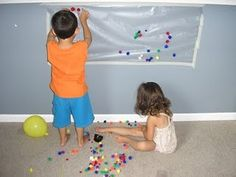 Tape contact paper to wall, and supply light items for sticking (pom poms, balloons, buttons).