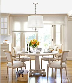 The kitchen's dining area features a simple, classic ceiling lamp plus window shades that allow for beautiful, filtered light.