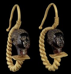 A pair of Roman gold and garnet African head earrings  Circa 1st-2nd Century A.D. Each composed of a finely carved garnet bead in the form of an African head with short incised hair, strung with double gold wire connected above and below to a tapering thick loop of twisted wire, the ear hook curving back on itself to form an s-shape, 1¾in (3.5cm) long including hook