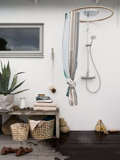 En vårdande sommardusch. Det randiga duschdraperiet BOLMÅN, design Synnöve Mork, mjukar upp känslan mot den egengjutna betongbänken och ger ett skönt skydd mot förbipasserande. GADDIS korg i två storlekar, FRÄJEN badlakan, SOCKERÄRT vas/kanna.