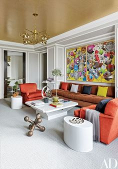 The family room ceiling is sheathed in a Maya Romanoff brushed-metal-leaf wallpaper. A riotous two-panel artwork by Keith Tyson overlooks a Sills-designed sofa in a Pollack fabric and a Fabrizio Cocchia cocktail table from Galerie Van den Akker | archdigest.com