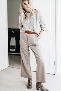 Camille Over The Rainbow wears a cozy sweater tucked into wide-leg pants, a tan leather belt, and snake-print boots