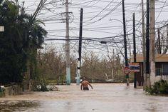 A man wades through a flooded road in Fajardo, Puerto Rico.