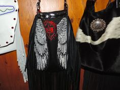 This bag is one that I had previously made and decided to adjust the size. The bag is made from a Hell and Back jacket that was brand new!  The wings on this are absolutely stunning with swarski crystals and leather hand cut fringe and an up-cycled belt.