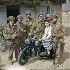 """Glider troops of """"D"""" Company, 2nd Battalion The Oxfordshire and Buckinghamshire Light Infantry, who had been on their way to DZ-W on the 8th or 9th June 1944 to collect supplies, pose for a photograph around a German DKW NZ 350 motorbike in Le Port with a local French girl. Left to right: Private Musty (with a German MP40 machine gun), CQMS Smith, Captain Priday, Unknown 12th Devonshires man, Corporal Lumbley and Private Gardner."""
