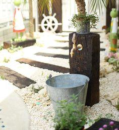今日は庭のアイデアをご紹介。庭はアイデアやアレンジ次第で、誰にでも楽しむことができます。ブロック塀をペンキで塗って、ステンシルでアクセント。天端には人工芝まで乗せています。これはレベル高いDIYですね~。これは枕木の立水栓。排水口を設置すると