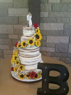 Barely naked cake with sunflowers and roses from Mad Batter Baker, Addison, TX. www.madbatterbaker.com   #MadBatterBaker  #NakedCake #CountryWedding #RusticChic #Sunflowers