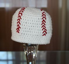 Paid pattern: Crochet Baseball Beanie.  I bet I could replicate this. Looks like a DC at the top, a SC for the bottom 4 or 5 rows, and you just whip-stitch from front to back to make the red baseball stitching.