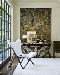 Antique tapestry, modern, sleek room and white and black butterfly-style chair.