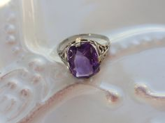 Wonderful ladies 10kt white gold filigree ring with a sweet amethyst colored glass stone. This dainty lady isnt in mint condition as her stone does have a flaw on the corner and is a bit loose, but she still wears beautifully as is or one could use the setting for their own stone! Shes right at a size 4 and weighs 1.5g. Very pretty ring made by one of my favorite jewelers, David Belais as he, in addition to being a great jeweler, was also the founder of the Humane Society of New York in…