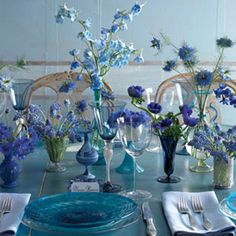The head table will feature various shapes and sizes of blue glassware (cobalt blue bottles, turquoise mason jars, blue bud vases, and turquoise hour glass vases) filled with an assortment of purple lisianthus, blue delphinium, purple hydrangeas, pale green succulents, purple hydrangeas, jasmine vine, purple stock flowers, and seasonal greenery, surrounded by silver mercury glass votives.