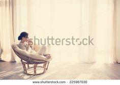 Young woman at home sitting on modern chair in front of window relaxing in her living room reading book and drinking coffee or tea, instagram toning - stock photo