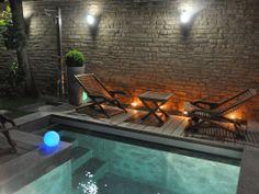La citadine par l'esprit piscine - 4 x 2 m Revêtement gris (pierre de Luzerne) Escalier droit Margelles en pierre de Luzerne Plage en ipé Trophée d'Or FPP 2011 de la piscine citadine de forme angulaire