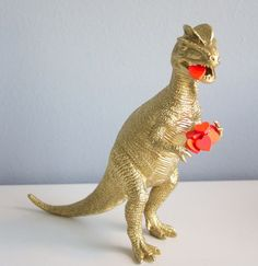 Heart-Eating Dinosaur. plastic dinosaur, gold paint and some sweetheart candies to do the trick.