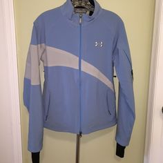 Under Armour cold gear running jacket NWOT. Took tags off but never wore. Baby/sky blue in color. (Leans more towards the purple family In pics posted.)  This jacket has so much to offer! It's tech ready. Has 2 zippered pockets on the outside. Has a big pocket on the inside that can hold your iPhone 6/6plus. Has smaller pocket on left hand sleeve that can hold an iPod or the older generations iPhones. Has opening for your earphones. Has zippered openings under each arm to let air in if your…