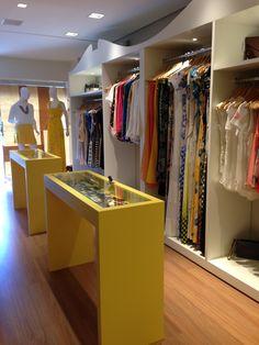Loja Roupa feminina por Amis Arquitetura - Armários brancos com desenhos vintage, aparadores para acessórios em laca amarela