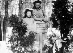 Olga and Tatiana at the grave of a family pet on Children's Island. All the Imperial pets were buried here for over 100 years.