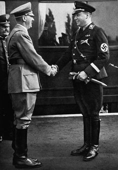 "Reich Minister Richard Walther Darre greets Hitler at the train station at the time of the harvest festival. Darré was a major force behind the Nazi policies of exploiting the conquered territories in the East. His ""race and space"" theories and his emphasis on eugenics were two of his most prominent ""achievements."" Darré was briefly imprisoned postwar and died in 1953."